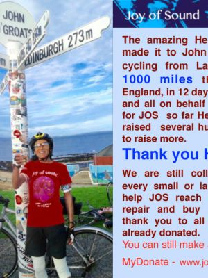 a photo of Hena Rohman with her bicycle by the John O'Groats signpost. She has cycled over a 1000 miles over twelve days from Land's End to raise money for Joy of Sound. Click picture for link